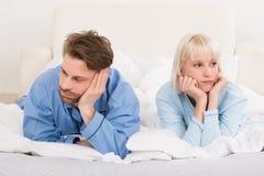Paare, die im Bett sich ignoriert liegen stockbilder