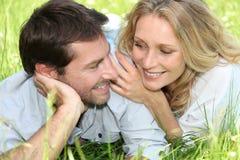 Paare, die im Gras liegen Lizenzfreie Stockfotos
