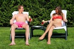 Paare, die im Hinterhof und in trinkenden Cocktails ein Sonnenbad nehmen Lizenzfreie Stockbilder