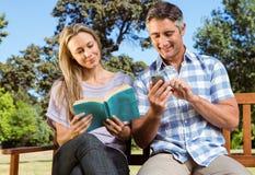 Paare, die im Park auf Bank sich entspannen Lizenzfreies Stockfoto