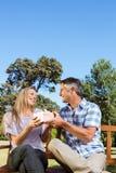 Paare, die im Park auf Bank sich entspannen Lizenzfreie Stockfotos