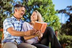 Paare, die im Park auf Bank sich entspannen Lizenzfreie Stockbilder