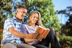 Paare, die im Park auf Bank sich entspannen Stockbilder