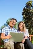 Paare, die im Park mit Laptop sich entspannen Lizenzfreie Stockfotos