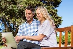 Paare, die im Park mit Laptop sich entspannen Stockfoto