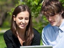 Paare, die im Park sitzen und Laptop verwenden Stockfotografie