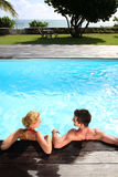 Paare, die im Pool sich entspannen Lizenzfreies Stockfoto