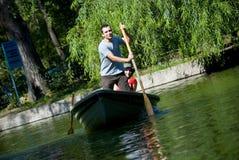 Paare, die im Rowboat schaufeln lizenzfreie stockbilder