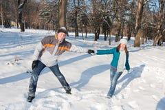 Paare, die im Schnee spielen Lizenzfreie Stockbilder