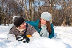 Paare, die im Schnee spielen Stockbilder