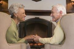 Paare, die im Wohnzimmer durch Kamin sitzen lizenzfreies stockbild