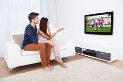 Paare, die im Wohnzimmer fernsehen Lizenzfreie Stockfotografie