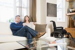Paare, die im Wohnzimmer sich entspannen Stockbild