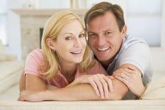 Paare, die im Wohnzimmer und im Lächeln sich entspannen stockfotos