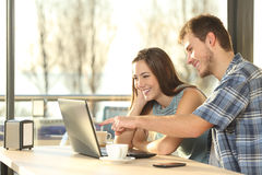 Paare, die Informationen in einem Laptop suchen lizenzfreie stockbilder