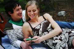 Paare, die am intelligenten Telefon in Verbindung stehen Lizenzfreie Stockfotos