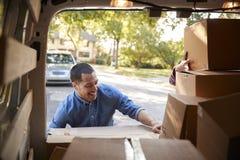 Paare, die Kästen von Van On Family Moving In-Tag entladen lizenzfreie stockfotografie