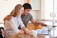 Paare, die Kaffee bei der Anwendung eines Laptops trinken Lizenzfreie Stockbilder
