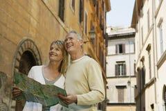 Paare, die Karte auf Straße in Rom halten Stockfoto