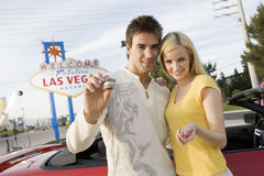 Paare, die Kasino-Chips With Car In The-Hintergrund halten Lizenzfreie Stockfotografie