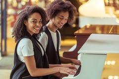 Paare, die Klavier spielen Stockfotos
