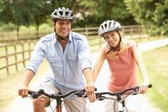 Paare, die in Landschaft-tragende Sicherheit Helme einen Kreislauf durchmachen Stockbilder