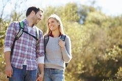 Paare, die in Landschafts-tragenden Rucksäcken wandern stockfotografie
