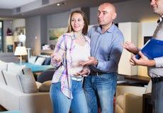 Paare, die Möbel im Salon wählen Lizenzfreie Stockfotos