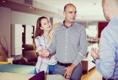 Paare, die Möbel im Salon wählen lizenzfreies stockbild