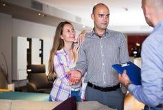 Paare, die Möbel im Salon wählen lizenzfreie stockbilder