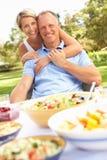 Paare, die Mahlzeit im Garten genießen Stockbilder