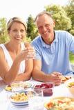 Paare, die Mahlzeit im Garten genießen Stockfotos