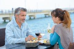 Paare, die Mahlzeit nahe bei Fluss essen Stockfoto