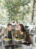 Paare, die Mahlzeit und Wein am Restaurant genießen Stockbilder