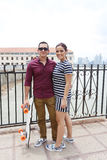 Paare, die, Mannholdingskateboard sich lieben stockbild