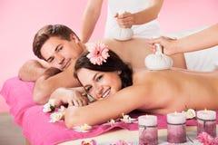 Paare, die Massage mit Kräuterkompressenbällen empfangen Lizenzfreie Stockfotografie