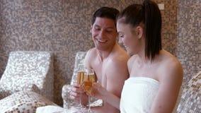 Paare, die mit Champagner im Badekurort rösten stock footage