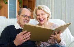 Paare, die mit Fotografiealbum sitzen Lizenzfreie Stockbilder