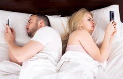 Paare, die mit Handys im Bett gesellig sind Lizenzfreie Stockbilder