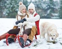 Paare, die mit Hund im Winter rodeln Lizenzfreie Stockfotografie