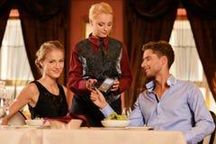 Paare, die mit Karte im Restaurant zahlen lizenzfreie stockfotos