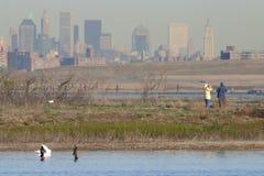 Paare, die mit Manhattan-Skylinehintergrund birding sind Stockfoto