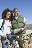 Paare, die mit Schaltplan und Mountainbiken stehen Stockbilder