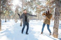 Paare, die mit Schnee im Winterpark spielen Stockfotos