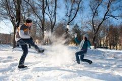 Paare, die mit Schnee spielen Lizenzfreie Stockfotografie
