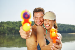 Paare, die mit Wasserwerfern im Sommer zielen stockbild