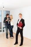 Paare, die nach Grundbesitz mit weiblichem Grundstücksmakler suchen Stockfotos