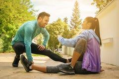 Paare, die nach Training ausdehnen Sie sitzend auf dem Bürgersteig stockbilder