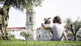 Paare, die nahe Baum auf Gras im Park küssen stock footage