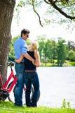 Paare, die nahe dem See mit Fahrrad stehen lizenzfreie stockbilder